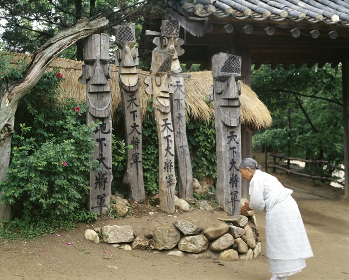 Elderly woman praying to guardian jangseung